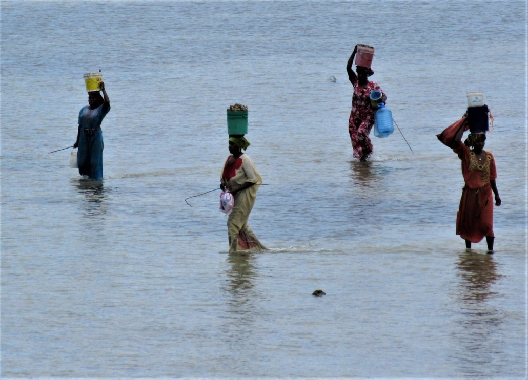 African women walking in water Zanzibar